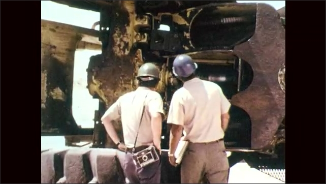 1970s: Men in hard hats walk around end of overturned front end loader, talk, peer inside, investigate, squat, point.