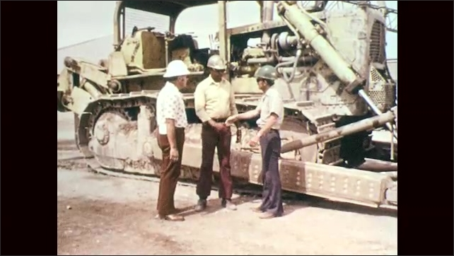 1970s: Man climbs down from construction equipment, shakes hands with two other men. Men talk.