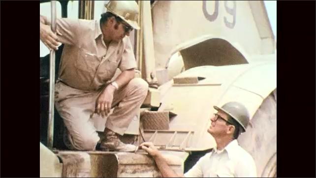 1970s: Man in hard hat talks. Man in hard hat kneels on construction equipment, looks down, talks to man on ground. Man walks down hill, holds tape.
