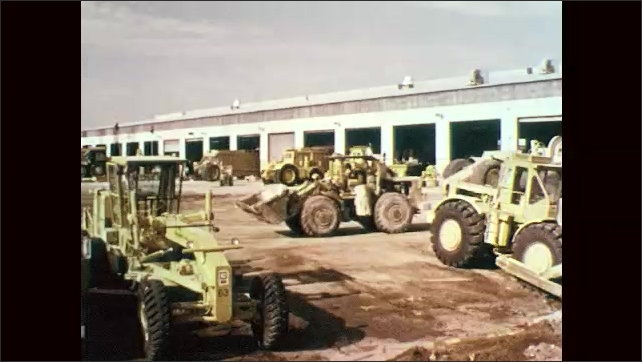 1970s: Man talks. People drive construction equipment around storage yard. Sign for heavy equipment maintenance. Man opens file cabinet drawer.