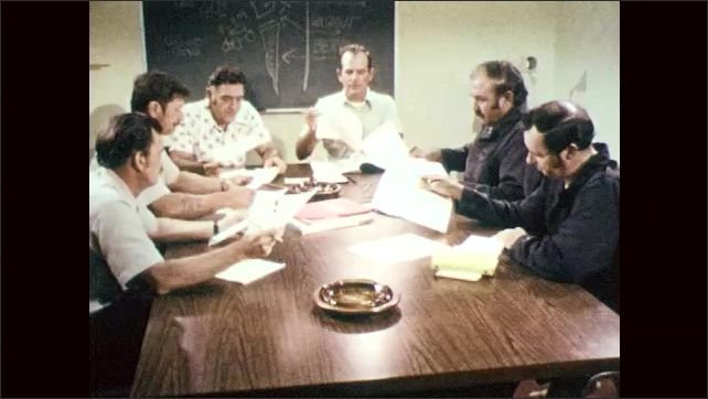 1970s: Men sit around conference table, look at papers, talk, write on papers.