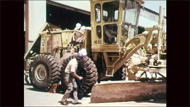 1970s: Men drives construction equipment down roads. Men inspect large construction vehicle. Women sit at desks in office, type on typewriters.