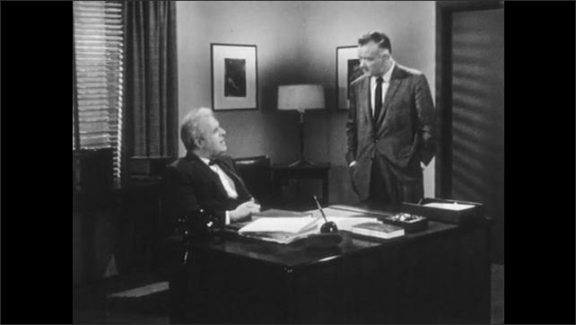 1950s: UNITED STATES: men speak in office. Man paces floor. Man puts hands in pockets.