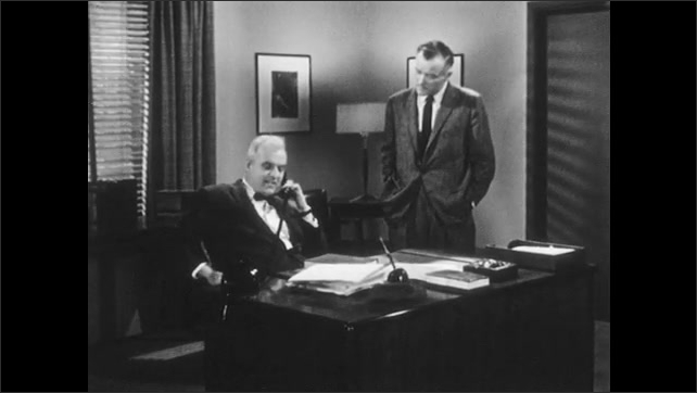 1950s: UNITED STATES: men speak in office. Man sits at desk. Man picks up telephone. Man speaks on phone.