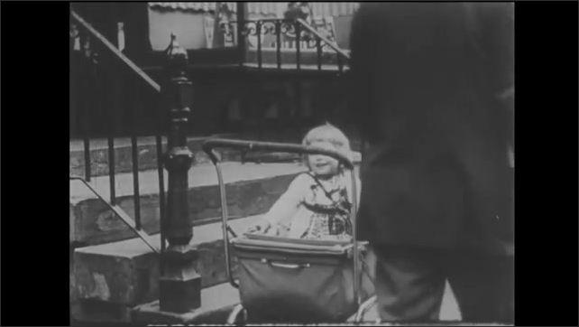 1940s: Boy rides bike behind horse drawn wagon in city street. Toddler sits in baby carriage on sidewalk. Woman extends arms and smiles. Woman approaches baby carriage and speaks.