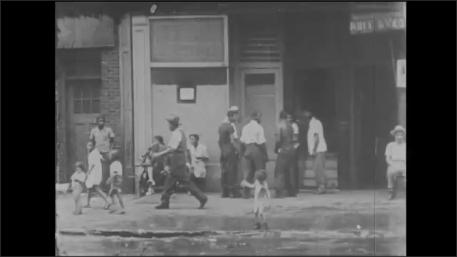 1940s: Child with box on head walks through water spray. Kids play in water spray from open hydrant. Woman shouts up to apartment window. Woman leans from apartment window and speaks.