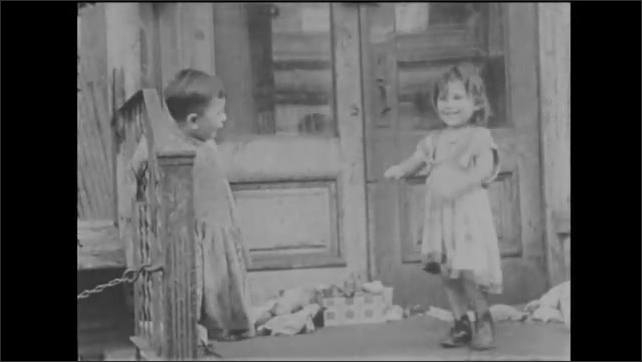 1940s: Girls and boys in costume dance in alley. Young children dance and hop on stoop. Girl leans against wall and laughs. Girls and boy dance wildly on stoop.