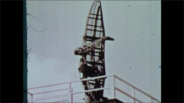 1960s: Waves from stormy sea crash ashore. Waves crash against docked boats. Man slides shelf out with measuring instrument on it. Storm waves. Radar dish. Man looks into radar display at hurricane.