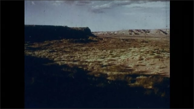 1960s: Boy walks on boulder, carries stick. Boy squints. Desert landscape. Boy squints. Desert rocks landscape.