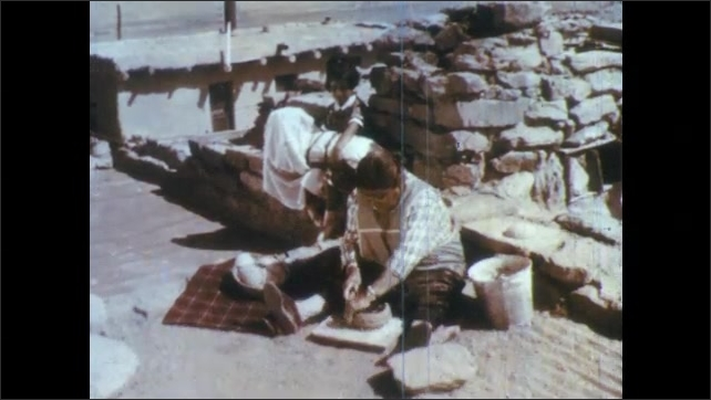 1960s: Young girl in pueblo smiles. Girl watches as woman mashes food in bowl. Woman wraps clay layer over top of bowl. Woman works on pot with rocks beyond. Woman wipes pottery seam, rolls clay.
