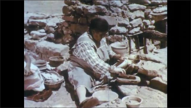 1960s: Hand takes pigment from mix on rock, traces thin line inside pottery bowl. Woman in pueblo paints bowl as young girl walks around her cradling baby. Hand paints bird inside bowl.