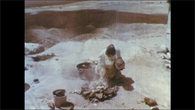 1960s: Woman paints bowl. Hand scatters pattern over bird painting. Young girl watches. Woman sets bowl aside. Woman crouches to smoking rocks, sets bowl over smoke. Woman moves rocks from hot pile.