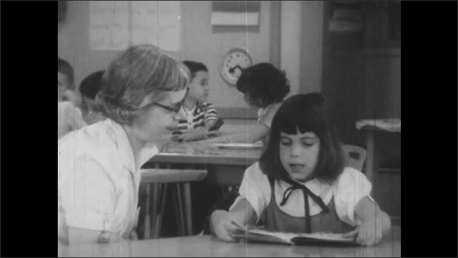 1950s: Pan of classroom, zoom in on woman reading with girl, zoom out to classroom.