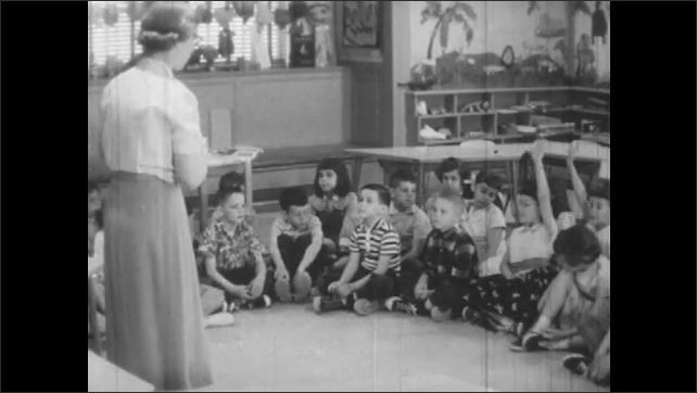 1950s: Woman stands in front of class, kids raise hands.