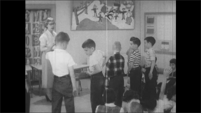 1950s: Woman talking to students, boys stand in front of class.