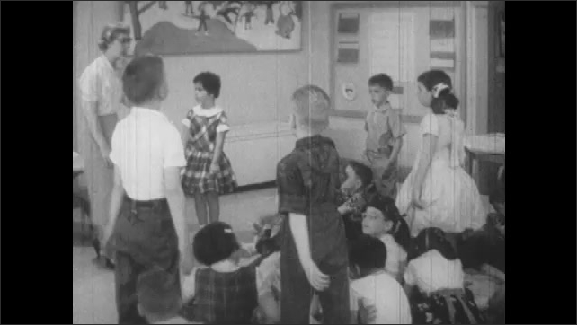 1950s: Woman stands in front of class, kids stand up. Woman talks to class.