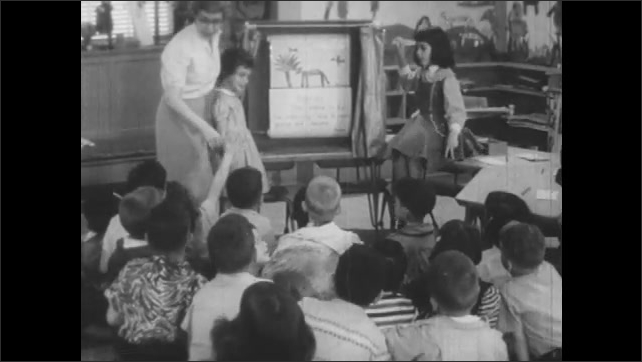 1950s: Kids enter classroom. Teacher in front of class, kids sit on floor. Girls by easel in front of class, kids raise hands.