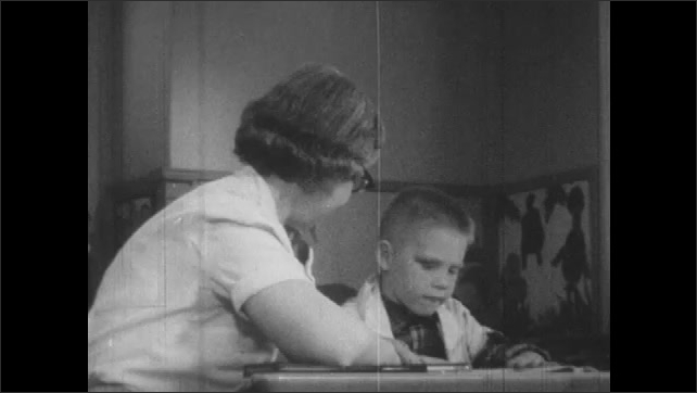 1950s: Pan across kids painting. Woman reading with boy at table. Woman and boy at table, zoom in on boy reading.