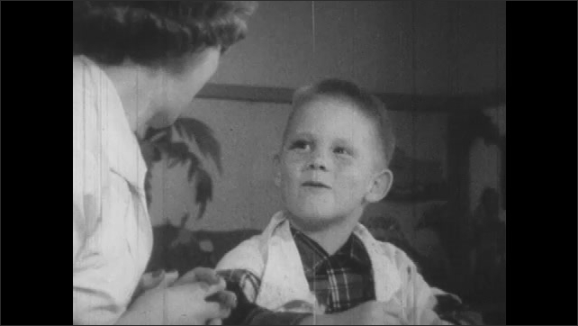1950s: Close up, boy reading at table, zoom out, woman and boy talk.