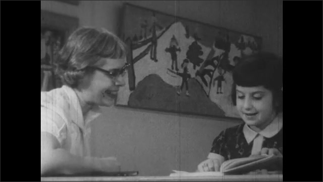 1950s: Little girl and woman look at book together.  Student and teacher speak.  Woman points at book.