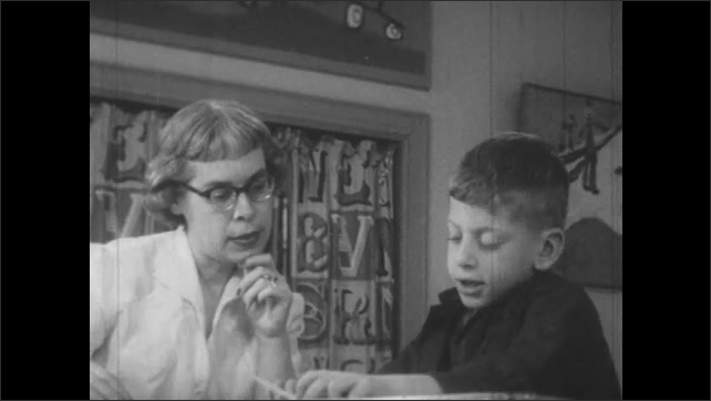 1950s: Teacher and little boy sit at table.  Boy reads.  Boy points.