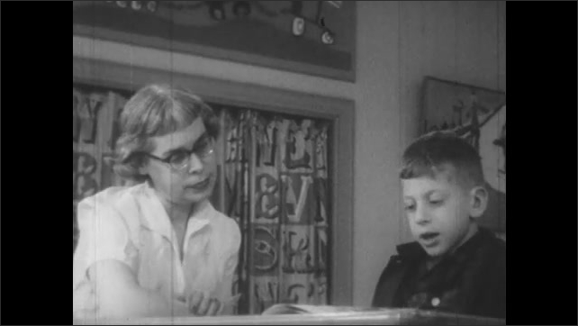 1950s: Teacher and little boy sit at table.  Boy reads.