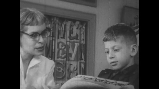 1950s: Classroom.  Students work at tables.  Children finger paint.  Teacher and little boy look at book and talk.