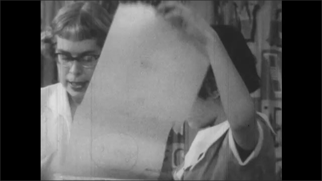 1950s: Woman makes note in book.  Teacher and little girl look at scroll of paper.  People speak.