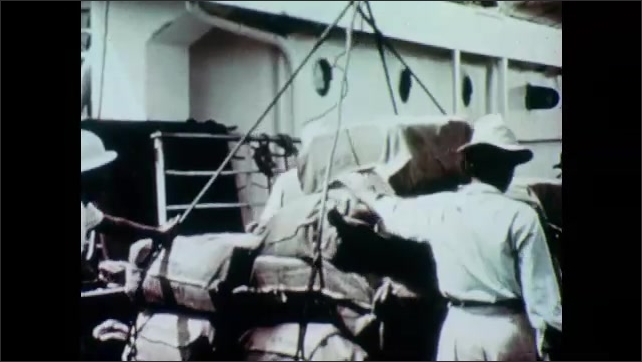 1950s: Men and women sit and type. Man welds. Cargo is unloaded from ship. Large ship at port.