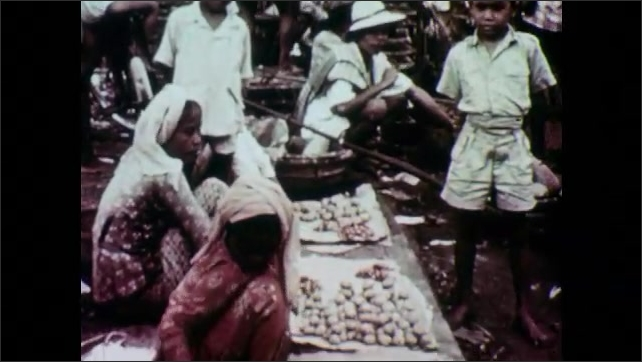 1950s: People work and walk in outdoor market. Building with sign for Djakarta. Cars drive on road, people move through city.