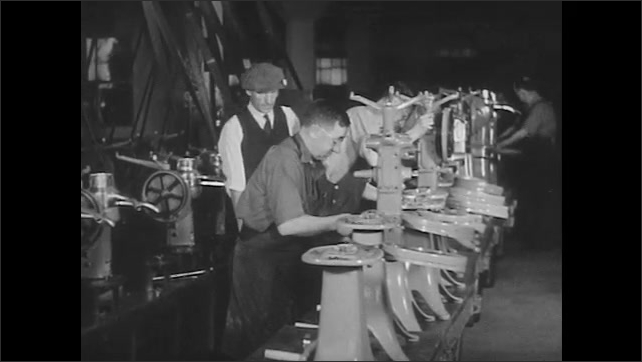 1950s: Men walk into industrial factory gates. Ford manufacturing plant. Men work on farm machinery assembly line. Train cars carry farm equipment from factory.