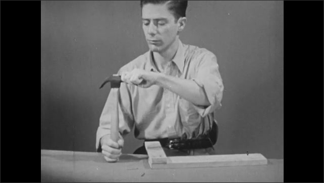1950s: man at table hammers wood, hands wiggle loose hammer head, hand pounds bottom of hammer on table, man uses 2nd hammer to knock off hammer head, places head back on hammer