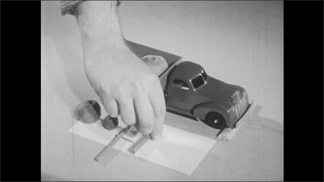 1950s: toy truck with clay and wooden rods in back runs into hand, rod rotates, hand put modeling clay in back of truck, inserts wooden rods, spins rod