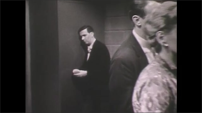 1960s: Well dressed group of men and women stand around talking, looking concerned, woman checks her watch. Man stands alone in corner looking withdrawn, worried.