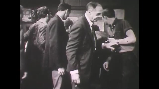 1960s: Man stands up, carries paper over to bulletin board. People gather to look. Man walks over to table of busy men and women to discuss papers.