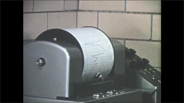 1960s: Man looks at spectrometer recording graph.