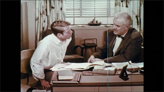 1960s: UNITED STATES: boy talks to man in office. Student talks with teacher. Man shows diagram to student