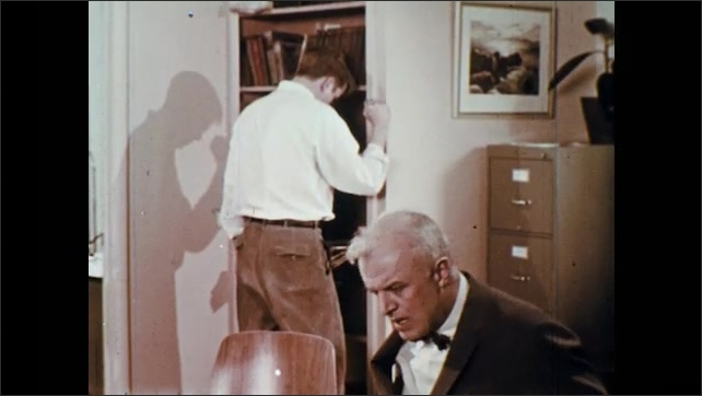 1960s: UNITED STATES: boy stands in office. Boy speaks with man. Teacher talks to student. Boy stands by cupboard door.