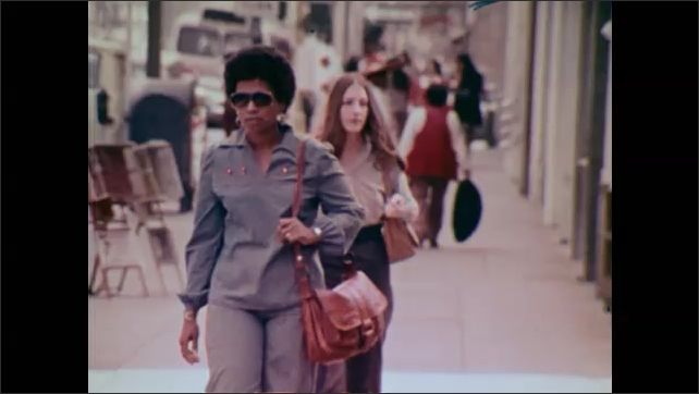 1980s: UNITED STATES: lady walks along street in sunshine. Lady in city. Lady holds diaphragm in hand.
