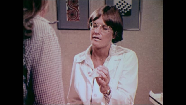 1980s: UNITED STATES: lady sits in clinic. Lady holds diaphragm in hand. Close up of diaphragm.