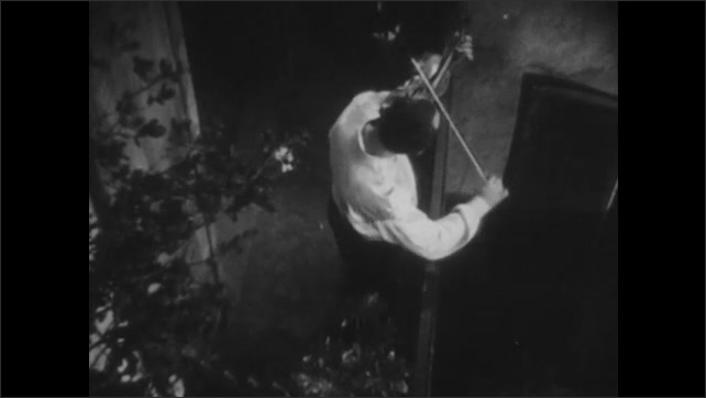 1940s: Woman opens doors and walks onto balcony. Woman sweeps near man playing clarinet. People play various instruments in windows of building. Woman speaks to woman standing on balcony.