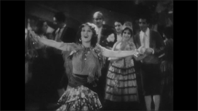 1940s: Woman in ruffled, Spanish style skirt sings opera on the stage amongst a cast of men. Woman sings the Habanera aria from Carmen while dancing.