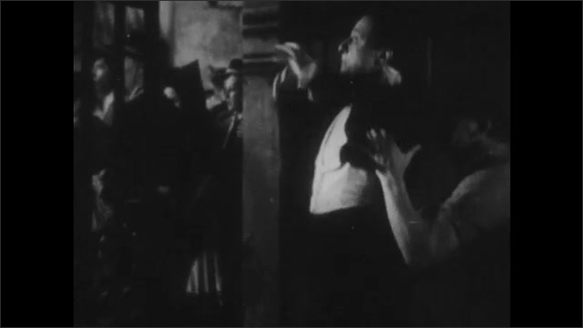1940s: Carmen sings seductively near the seated man in uniform. Man in the wings of the stage is outraged and has to be held back.