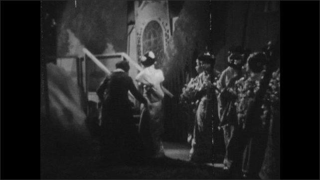 1940s: Chorus girls move aside for the lead soprano to enter from the wings. Lead soprano enters on the stage through the pagoda.