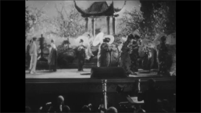 1940s: Star soprano descends the pagoda stairway singing. Cast of women circle, twirling their parasols.