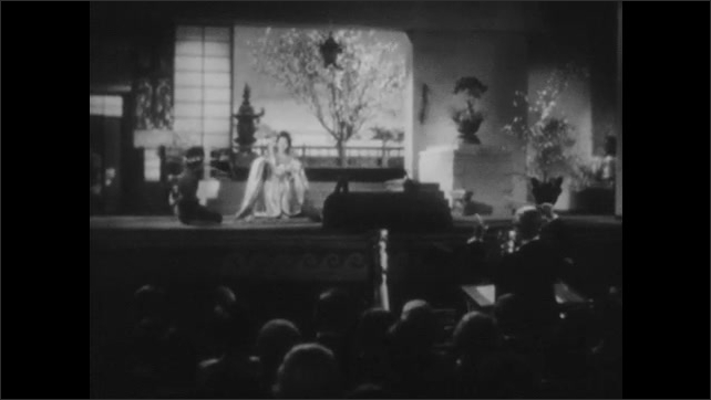 1940s: Star soprano kneels and sings on the stage.