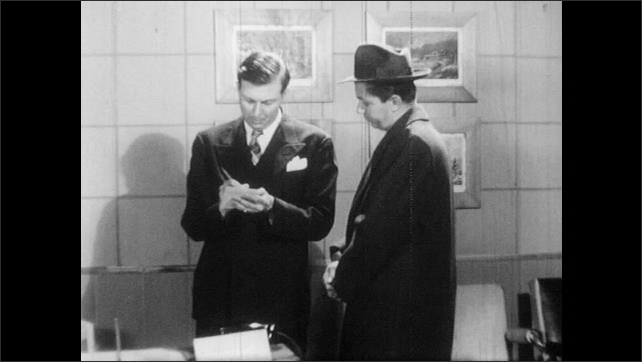 1950s: Salesman with notepad and pencil talks with man in store.