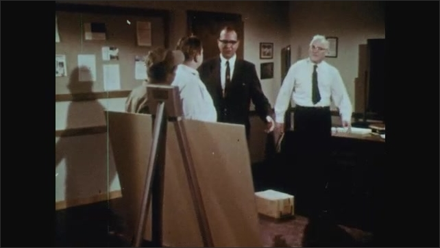 1960s: UNITED STATES: man in suit talks to man in uniform in room. Man enters room. Man in suit with glasses.