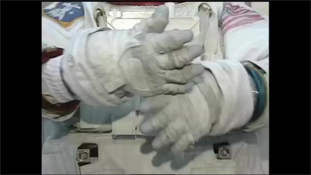 1990s: Low angle, space station part moving in lab. Low angle pan of space station part. Hands adjusting gloves, tilt up to astronaut in space.