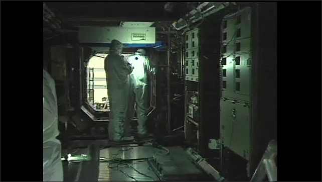 1990s: Workers by space station part in lab. Pan across space station part. Zoom out, workers inside component. Men working in spacecraft, zoom in. Hand points to buttons. Man opens equipment.
